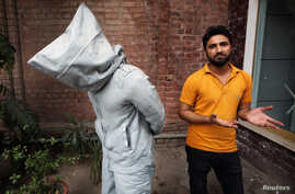 "Saud Baloch, 28, a fine art artist, stands near his sculpture called ""No Fear"" during an interview at the National College of Arts in Lahore, Pakistan, March 22, 2013"