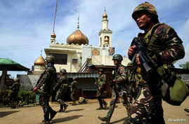 Government troops walk past a mosque before their assault with insurgents from the so-called Maute group, who have taken over large parts of Marawi City, southern Philippines, May 25, 2017.