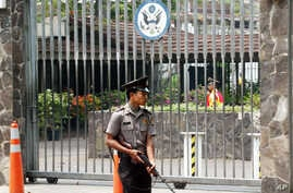 FILE - An armed Indonesian police officer stands guard at the gate of the U.S. embassy in Jakarta, Indonesia.