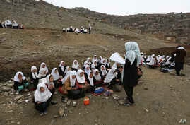In this April 5, 2017 photo, Afghan students attend school classes in an open air primary school on the outskirts of Kabul, Afghanistan.