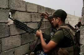 A soldier with the Iraqi special forces reloads his weapon on a rooftop in west Mosul as fighting between Iraqi troops and the Islamic State group continues,  April 23, 2017.