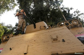 An Egyptian army soldier stands guard atop an armored personnel carrier as he talks on his mobile phone in Giza, south of Cairo, Aug. 19, 2013.