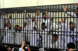 Supporters of former Egyptian president Mohamed Mursi, standing trial on charges of violence that broke out in Alexandria last year, react after two fellow supporters were sentenced to death, in a court in Alexandria, March 29, 2014.