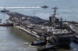 FILE - The nuclear-powered aircraft supercarrier USS George Washington is escorted into a navy port in Busan, South Korea, Oct. 4, 2013.
