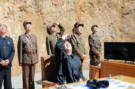 This image made from video of a news bulletin aired by North Korea's KRT on July 4, 2017, shows what was said to be North Korea leader Kim Jung Un, center, watching the launch of a Hwasong-14 intercontinental ballistic missile, ICBM, in North Korea's