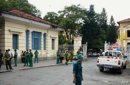 Policemen and security staff stand outside the main entrance gate of Ho Chi Minh City's People's Court where three bloggers stand trial for 'anti-state propaganda' on September 24, 2012.