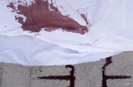 The blood of a Syrian civilian, killed by a Syrian Army sniper, is seen on the sidewalk outside Dar el-Shifa Hospital in Aleppo, September 27, 2012.
