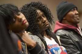 Family members of Freddie Gray - sister Fredricka Gray, left, mother Gloria Darden, center, and stepfather Richard Shipley - listen during a news conference after a day of unrest following the funeral of Freddie Gray in Baltimore, April 27, 2015.