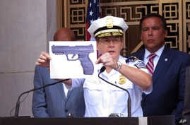 Columbus, Ohio, Police Chief Kim Jacobs holds up a photo showing the type of BB gun that police say a 13-year-old boy pulled from his waistband just before he was shot and killed by police investigating an armed robbery report, Sept. 15, 2016. Police