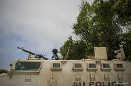 A Ugandan police officer serving with the African Union Mission in Somalia's first Formed Police Unit stands at the top of an armored personnel carrier at a police station in the capital Mogadishu, August 7, 2012.