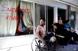 Wes Allen Jr., from left, sits with his father, Wes, his sister, Alison and his mother, Vicki, outside their room at a damaged motel, Oct. 16, 2018, in Panama City, Fla., where many residents continue to live in the aftermath of Hurricane Michael. Ma