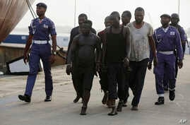 FILE- In this Feb. 22, 2016, photo, Nigeria Naval officers walk along with arrested pirates that hijacked the Panama-flagged Maximus vessel after it was rescued.