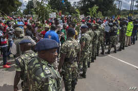 FILE - Demonstrators in Malawi rally in an anti-government protest as members of the country's security forces look on, in Lilongwe, Malawi, April 27, 2018.