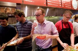 FILE - Steve Ells, center, CEO of Chipotle Mexican Grill, eats a burrito at a New York Chipotle restaurant. The chain's loaded chicken burrito contains 2,790 mg of sodium.