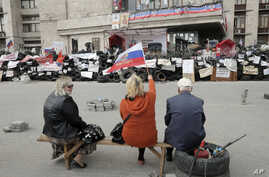 Pro-Russian activists with Russian flag sitting at a barricade at the regional administration building in Donetsk, Ukraine, April 23, 2014.