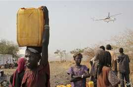 In this photo taken Wednesday, Feb. 26, 2014, a displaced South Sudanese woman carries a plastic jerry can with water in the United Nations camp that has become home to thousands of displaced people in Malakal, South Sudan. (AP Photo/Ilya Gridneff)