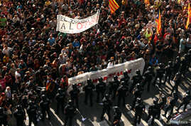 Catalan separatist protesters stand in front of Mossos d'Esquadra police officers in Barcelona, Spain, Sept. 29, 2018, before clashing during a protest against a demonstration in support of the Spanish police units who took part in the operation to p
