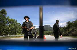 FILE - Members of the General Operations Force control the checkpoint on the road near the area where the abandoned human trafficking camp was discovered in the jungle close to the Thailand border at Bukit Wang Burma in northern Malaysia May 28, 2015