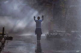 FILE - An opposition MDC party supporter hold his hands up after being sprayed with a water canon and in clouds of teargas on a street in Harare during clashes with police, Aug. 1, 2018.