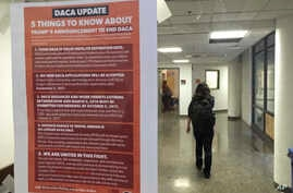 A student walks past a tip sheet for Deferred Action for Childhood Arrivals recipients who fear deportation that is taped to a window on the University of California, Berkeley campus in Berkeley, California, Sept. 7, 2017. Colleges and universities n