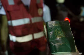 FILE - A rescuer holds a waterlogged Pakistani passport as bodies of migrants who drowned off the coast of Zuwara, Libya, are collected, Aug. 27, 2015.