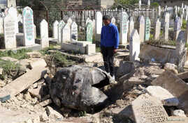 FILE - A man looks down at an unexploded barrel bomb dropped by forces loyal to Syria's President Bashar al-Assad at a cemetery in the al-Qatanah neighbourhood of Aleppo March 27, 2014.