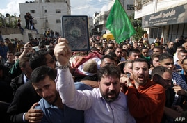A mourner holds the Koran, Islam's holy book, in front of Palestinians carrying the body of one of five Palestinians killed by Israeli security forces following attempted stabbing attacks, during a funeral procession in Hebron, West Bank, Oct. 31, 20...
