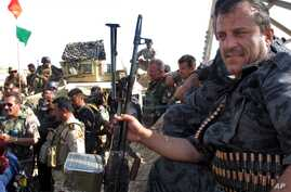 File - Members of the Kurdish security forces gather in an area in Kirkuk, Iraq. In Iraq's chaos, the Kurds are emerging as significant winners, June 14, 2014.