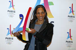 French track and field sprinter Christine Arron holds the logo as she attends the presentation of the Paris candidacy for the 2024 Olympic and Paralympic Games in Paris, Feb. 17, 2016.