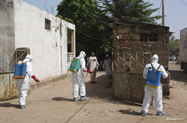 Health workers spray disinfectant at a mosque, in Bamako November 14, 2014. A local government official said the body of a Guinean imam, suspected of dying from the Ebola virus on October 27, was washed at the mosque before his funeral. Mali is traci