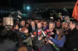 Can Dundar, the editor-in-chief of opposition newspaper Cumhuriyet, center right, and Erdem Gul, the paper's Ankara representative, center left, speak to the media outside Silivri prison near Istanbul, after their release early Friday, Feb. 26, 2016.