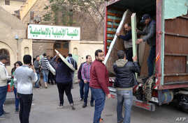 Egyptian Coptic Christians unload their belongings from a truck as they arrive to take refuge at the Evangelical Church in the Suez Canal city of Ismailia, Feb. 24, 2017.
