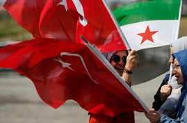 Members of a Turkish pro-government aid group, carrying Syrian and Turkish flags, wait for the departure of trucks carrying humanitarian aid destined for Idlib, Syria, in Istanbul, Sept. 10, 2018. The convoy of 20 vehicles will attempt to reach Syria