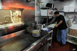"""FILE - Carlos Chavez, works in the kitchen by of his restaurant by himself on """"A Day Without Immigrants,"""" July 1, 2011, in Atlanta. Chavez gave his workers the day off, however with other restaurant owners open he decided he couldn't afford to remain"""