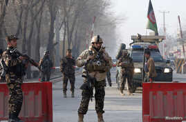 Afghan security forces keep watch at a check point close to a compound of Afghanistan's national intelligence agency in Kabul, Afghanistan, Dec. 25, 2017.