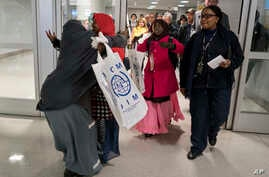 Halima Mohamed, embraces her daughter Muzamil Shalle, 14, left, as her other daughter Miski Shalle, 11, center, approaches. Mohamed sees her children for the first time in seven years in New York, March 8, 2017. The parents, who are from Somalia, but
