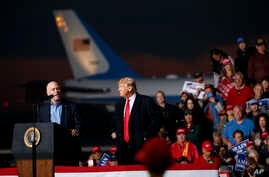 Rep. Greg Gianforte, R-Mont., speaks as President Donald Trump stands right during a campaign rally at Minuteman Aviation Hangar, Oct. 18, 2018, in Missoula.