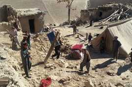 Rescuers have struggled to reach quake-struck zones like this one, where Afghan men remove personal belongings from Takhar province homes, northeast of Kabul, Oct. 27, 2015.
