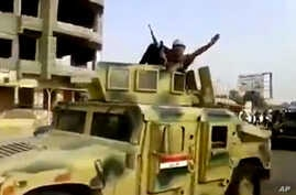In this Tuesday, June 17, 2014 image taken from video uploaded to a militant social media account, which has been authenticated based on its contents and other AP reporting, an al-Qaida-inspired Islamic State of Iraq and the Levant militant waves as