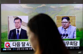 A visitor walks by a TV screen showing file footage of South Korean President Moon Jae-in, left, and North Korean leader Kim Jong Un, right, during a news program at the Seoul Railway Station in Seoul, South Korea, March 29, 2018.