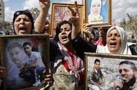 Palestinian women hold portraits of relatives held in Israeli jails, West Bank city of Nablus, 6 Oct. 2009