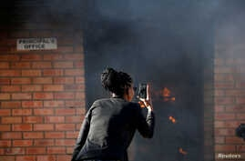 FILE - A women uses a cellphone to take pictures of a burning principal's school office in Mashau Dolly village in South Africa's northern Limpopo province, May 5, 2016.