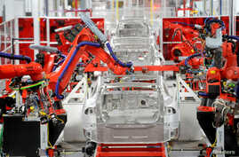 FILE - Robotic arms assemble Tesla's Model S sedans at the company's factory in Fremont, California, June 22, 2012.