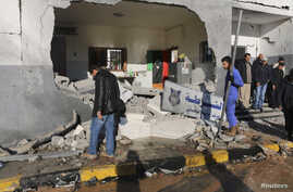 Civilians and security personnel stand at the scene of an explosion at a police station in Tripoli, Libya, a blast later claimed by militants professing loyalty to Islamic State, March 12, 2015.