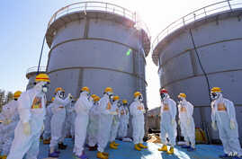 Japanese Prime Minister Shinzo Abe, third right, wearing a red helmet, is briefed about tanks containing radioactive water by Fukushima Dai-ichi nuclear power plant chief Akira Ono, fourth right, during his inspection tour to the tsunami-crippled pla