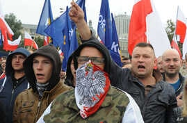 FILE - Protesters shout anti-migrant slogans as several thousand right-wing nationalists rally, demonstrating against EU proposed quotas for Poland to spread the human tide of refugees around Europe, in Warsaw, Poland, Sept. 12, 2015.