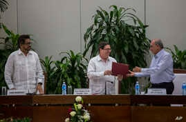 Cuba's Foreign Minister Bruno Rodriguez, center, gives a copy of the peace accord to Humberto de La Calle, right, head of Colombia's government peace negotiation team, as Ivan Marquez, left, chief negotiator of FARC, watches, after the signing of the
