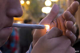 A young man lights a marijuana cigarette during a demonstration demanding a new law on cannabis in Montevideo, May 8, 2013.
