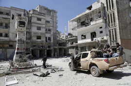 Rebel fighters inspect a site damaged by what activists said was shelling by warplanes loyal to Syria's President Bashar al-Assad in Jisr al-Shughour town, after the rebels took control of the area, April 26, 2015.