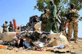 South Sudan army soldiers stand next to a destroyed motorcycle near Bor Airport, northwest of capital Juba, Dec. 25, 2013.